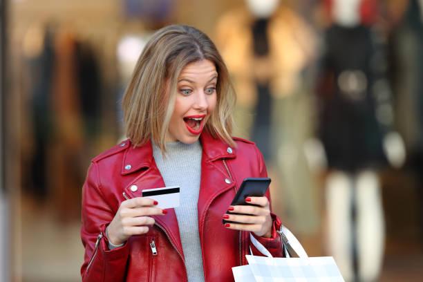 überrascht shopper zahlen auf linie in einem einkaufszentrum - die besten apps stock-fotos und bilder