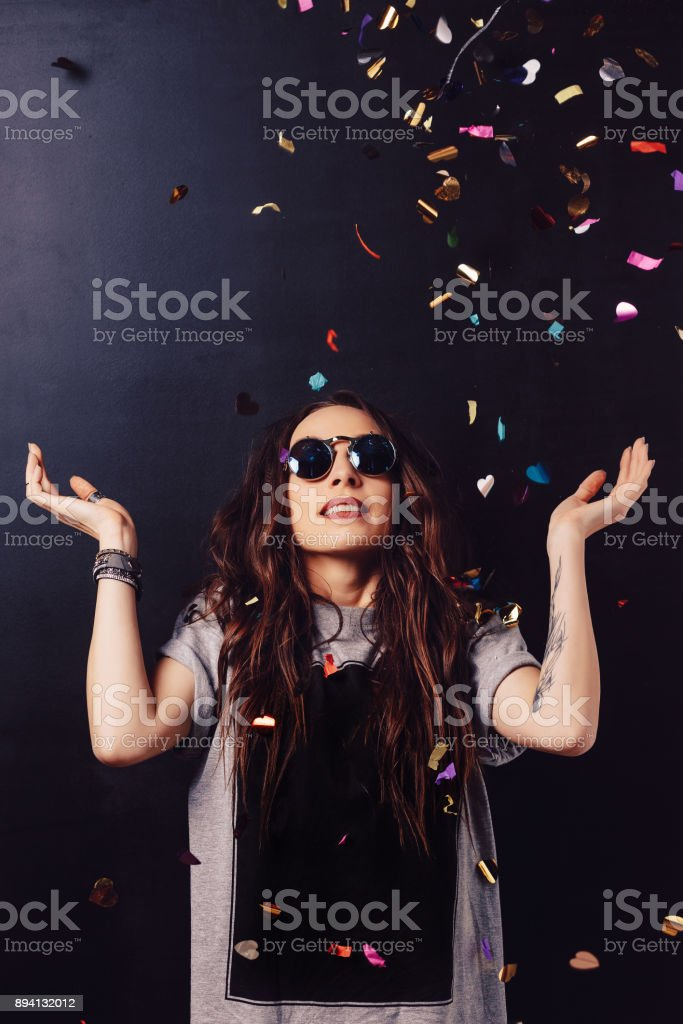 Surprised smiling girl surrounded by confetti stock photo