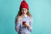 istock surprised street girl in glasses, red cap. blue shirt looking at the smartphone 1127487944