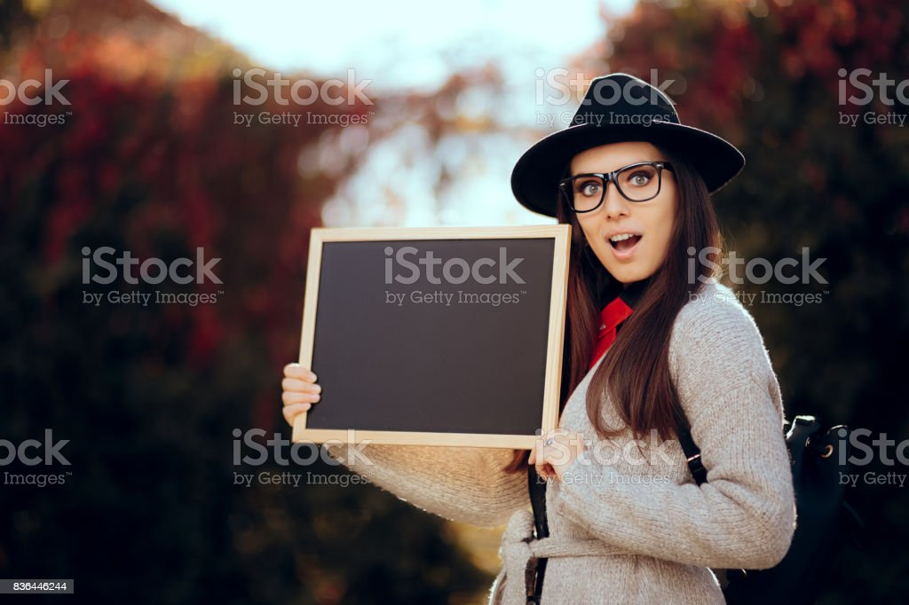 Surprised Student Holding a Blackboard Sign Sale Announcement stock photo
