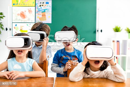 682285886 istock photo surprised students with virtual reality headset in classroom 900075792