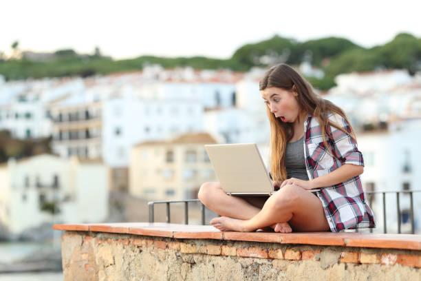überrascht teen suche nach online-bietet auf einem laptop - schnell lesen lernen stock-fotos und bilder