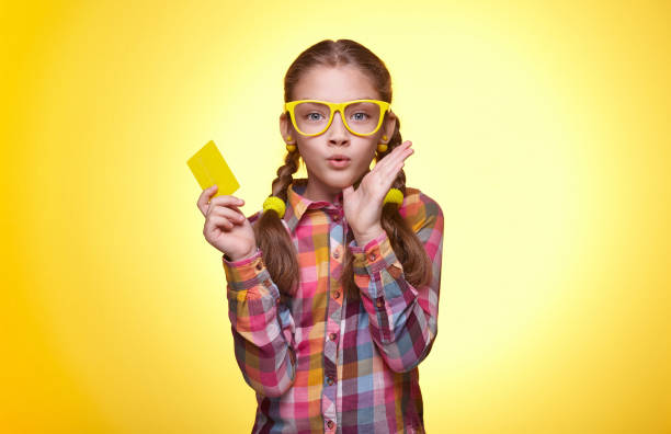 Surprised teen girl with credit card over yellow background Teenager with a credit card, surprised face, children's emotions, girl with glasses, bright plaid shirt, beautiful young lady, portrait of a young girl nerd hairstyles for girls stock pictures, royalty-free photos & images
