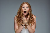 Surprised woman against gray background