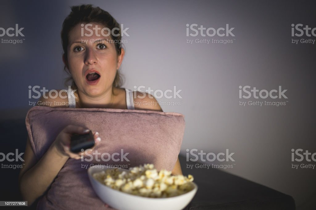Surprised woman by what she saw on TV stock photo