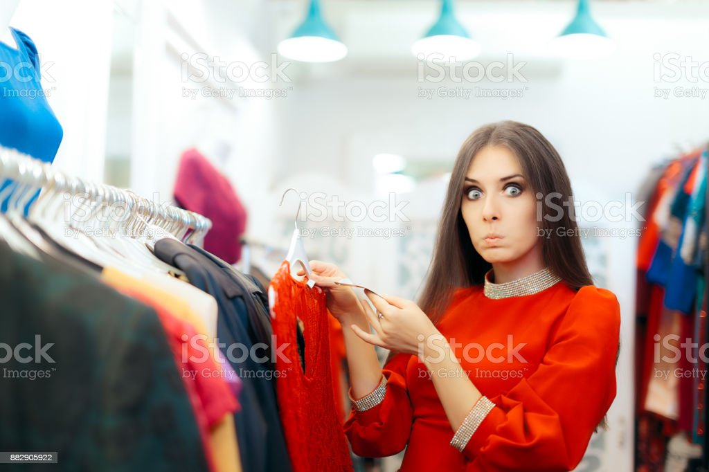 Surprised  Woman Checking Price Tag on a Dress in Sale Season stock photo