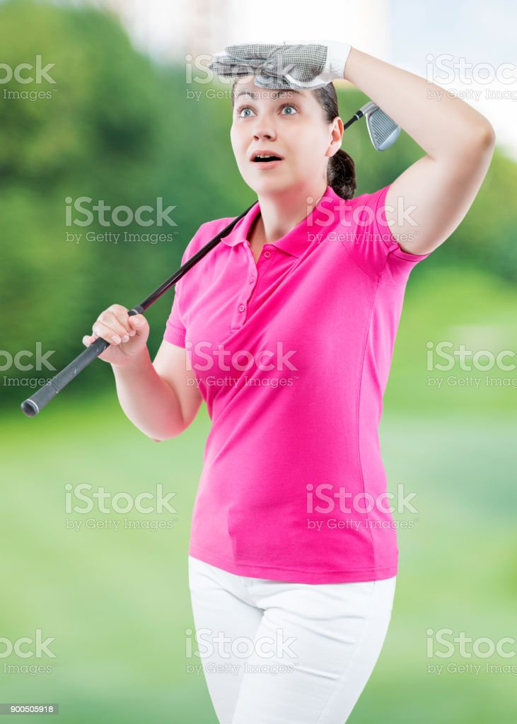 Surprised woman golfer looking where the ball flew away on a background of golf courses stock photo