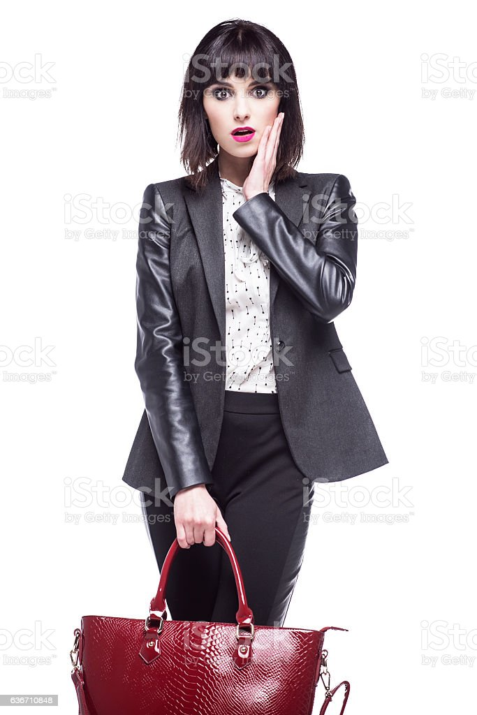 Surprised woman in a business suit on a white background. stock photo