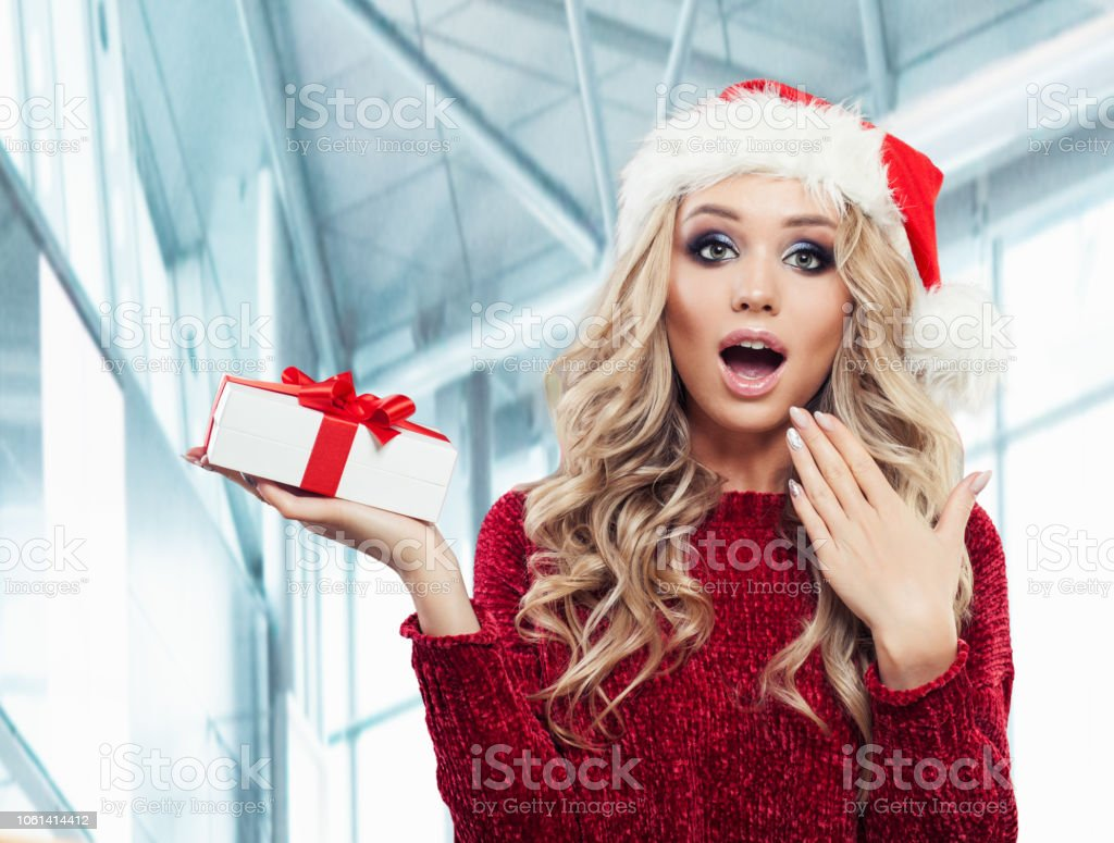 Surprised woman in Santa hat with Xmas gift box on office background....
