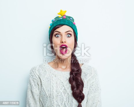 Studio portrait of excited young woman in winter outfit -  sweater and green woolen cap, staring at camera with mouth open. White background.