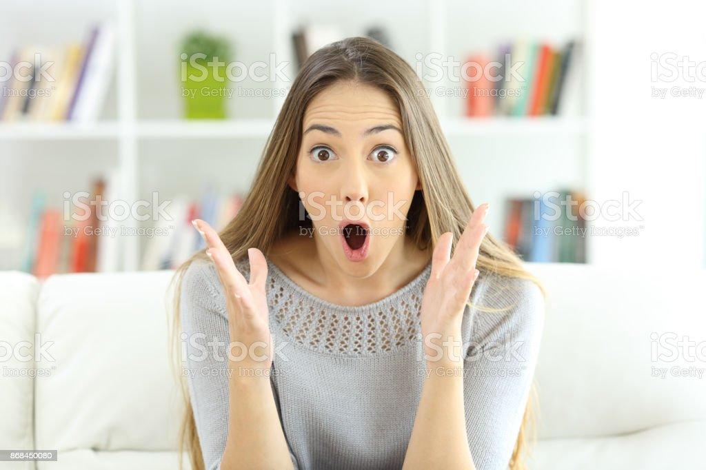 Mujer sorprendida mirando a cámara en casa - foto de stock