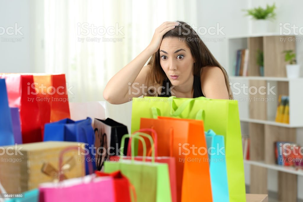 Surprised woman looking at multiple purchases royalty-free stock photo