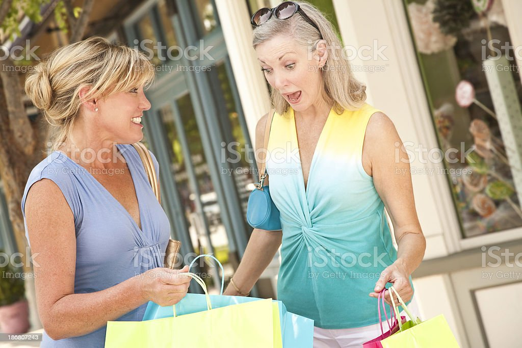 Surprised Woman Looking at Purchases in Shopping Bag royalty-free stock photo