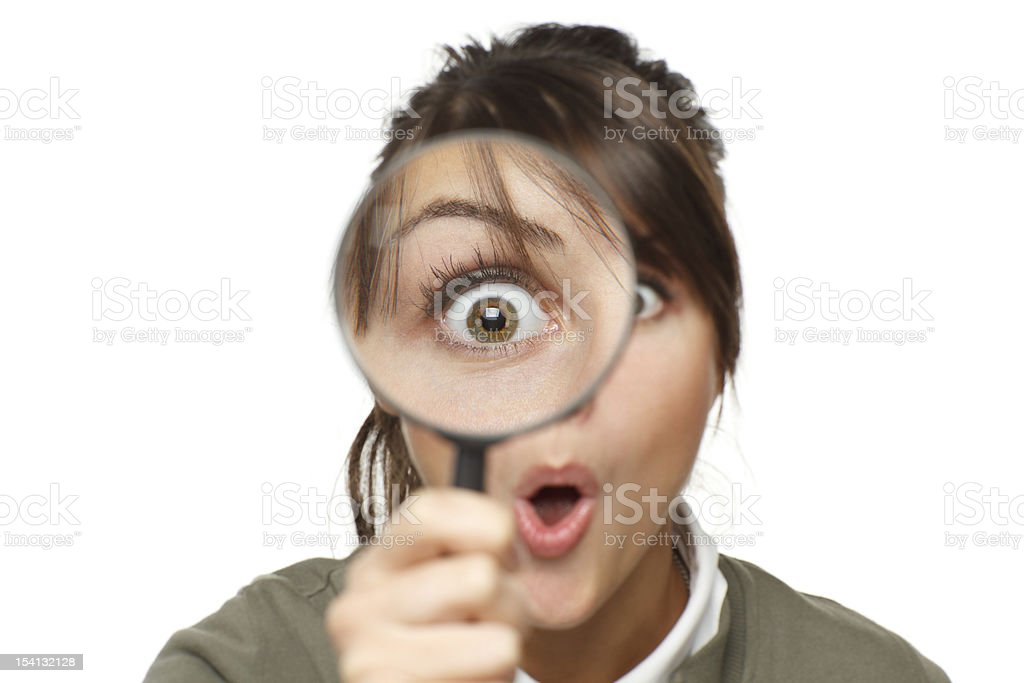 Surprised woman looking through a magnifying glass at you stock photo
