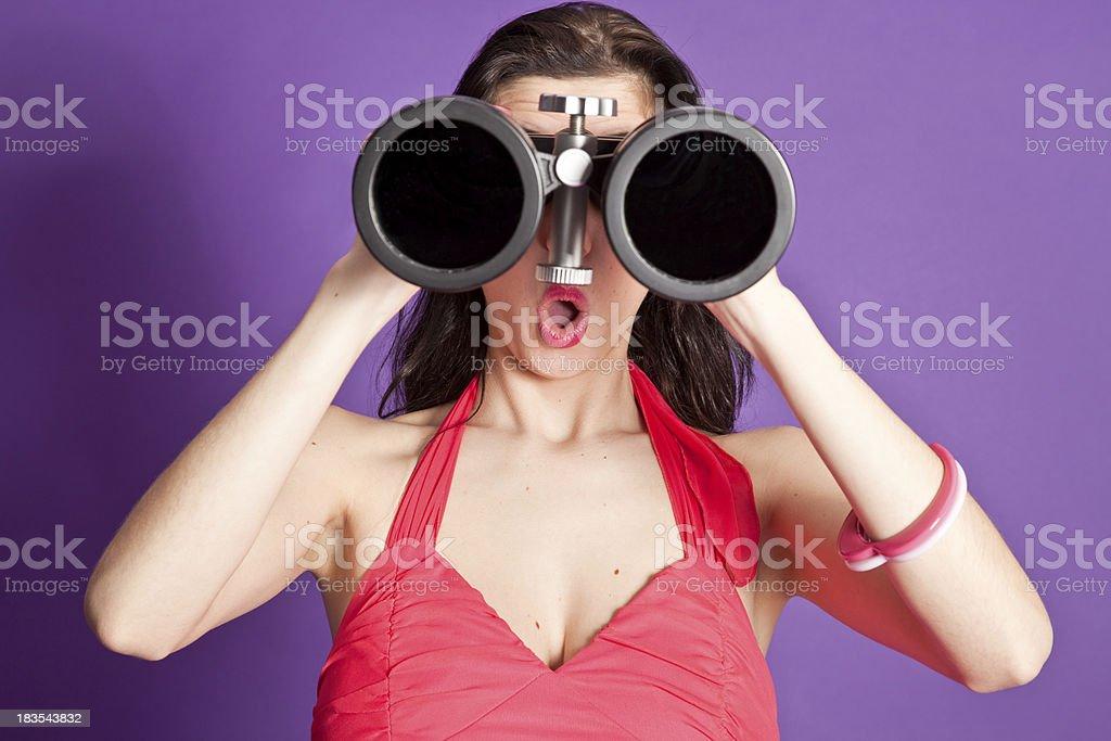 Surprised woman looking through large binocular stock photo