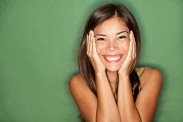 Surprised woman on green background. stock photo