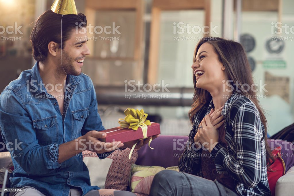 Surprised woman receiving Birthday present from her boyfriend. stock photo