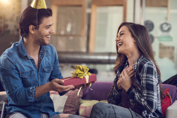 surprised woman receiving birthday present from her boyfriend. - birthday gift stock photos and pictures