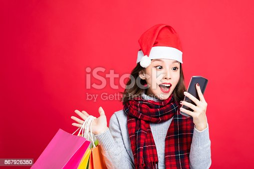 istock surprised Woman shopping for christmas gifts and watching smart phone 867926380