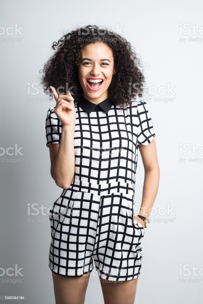 Surprised woman showing copy space Vertical portrait of cheerful young woman in casual wear pointing away on gray background. Surprised female in stylish outfit pointing away. 20-24 Years Stock Photo