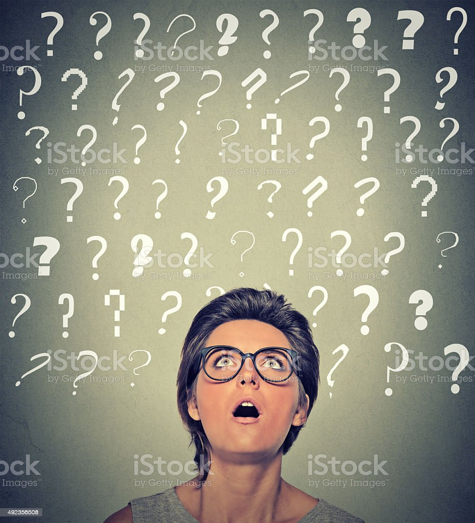 surprised woman with glasses looking up on many question marks stock photo