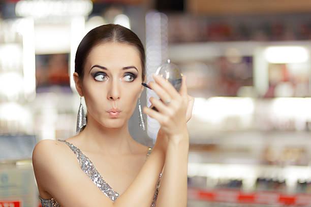 überrascht frau, die mit wimperntusche und make-up-spiegel - anzieh nacht stock-fotos und bilder