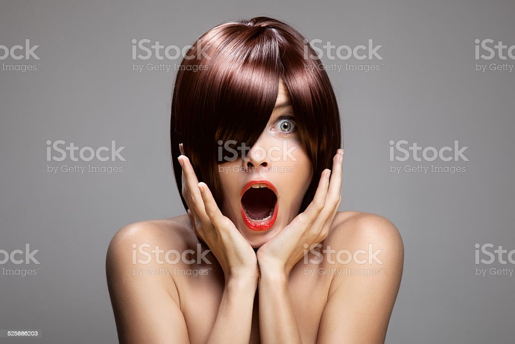 Surprised woman with perfect long glossy brown hair. stock photo