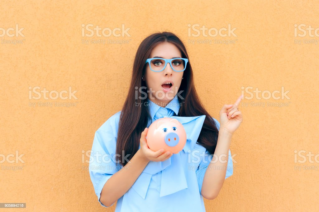 Surprised Woman with Piggy Bank thinking what to Invest in stock photo