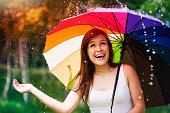 istock Surprised woman with umbrella during summer rain 179013209
