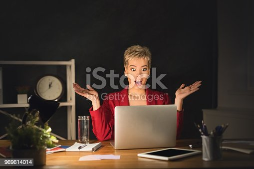 692461598 istock photo Surprised woman working on laptop late at night at office 969614014