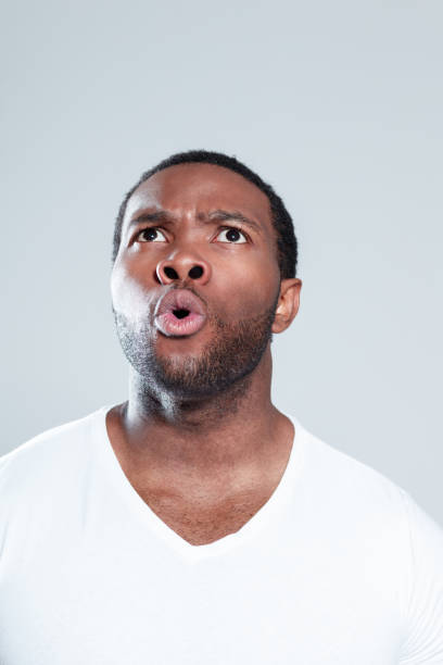 Surprised young african man looking away Close up portrait of surprised young african man looking away against gray background gasping stock pictures, royalty-free photos & images