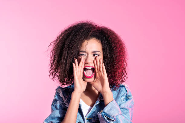 Surprised young afro woman shouting Studio portrait of cute young afro woman shouting, looking away. Pink background. rolling eyes stock pictures, royalty-free photos & images