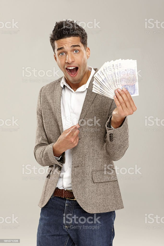 Surprised young businessman pointing at money stock photo