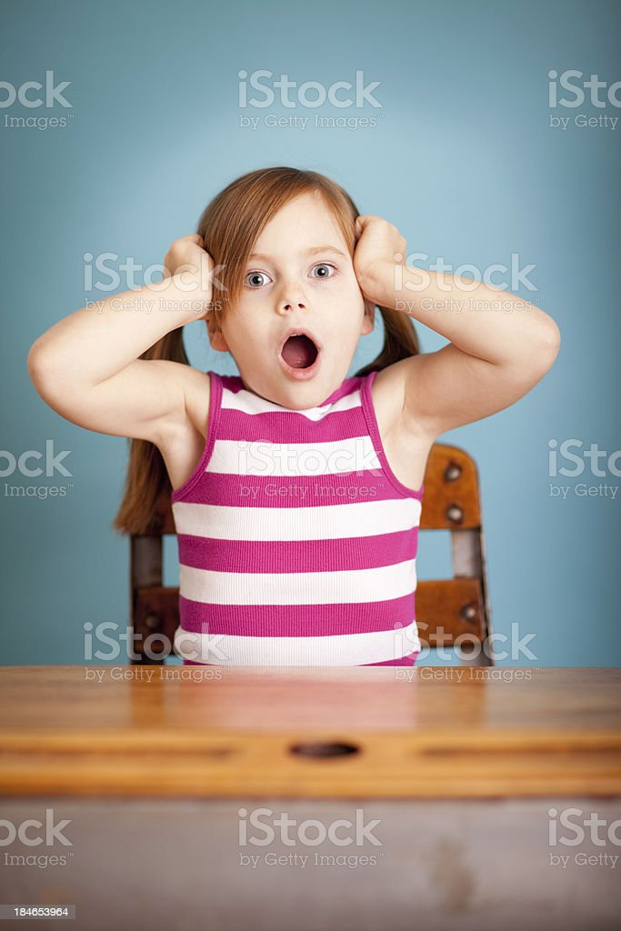 Surprised Young Girl Student Sitting at School Desk stock photo
