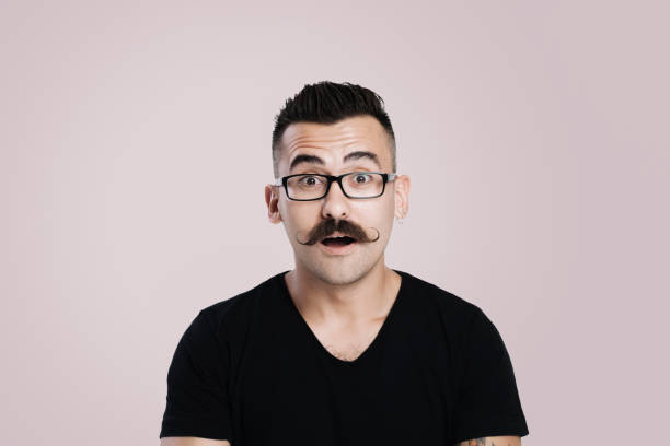 Surprised Young man with mustache Young male with glasses and mustache, grey background, studio shot, raised eyebrow, surprised, open mouth mustache stock pictures, royalty-free photos & images