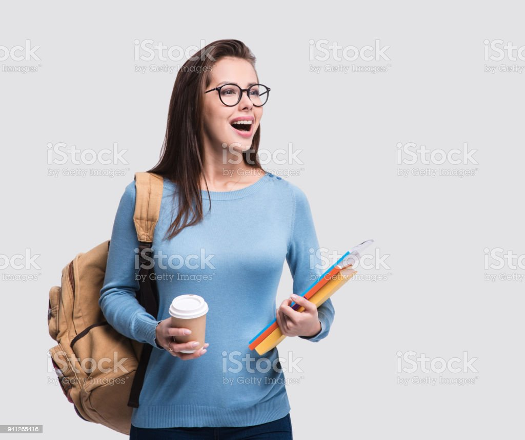 Surprised young student girl holding coffee and books stock photo