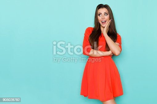 Beautiful young woman in red mini dress is holding hand on chin, looking away and laughing. Three quarter length studio shot on blue background.