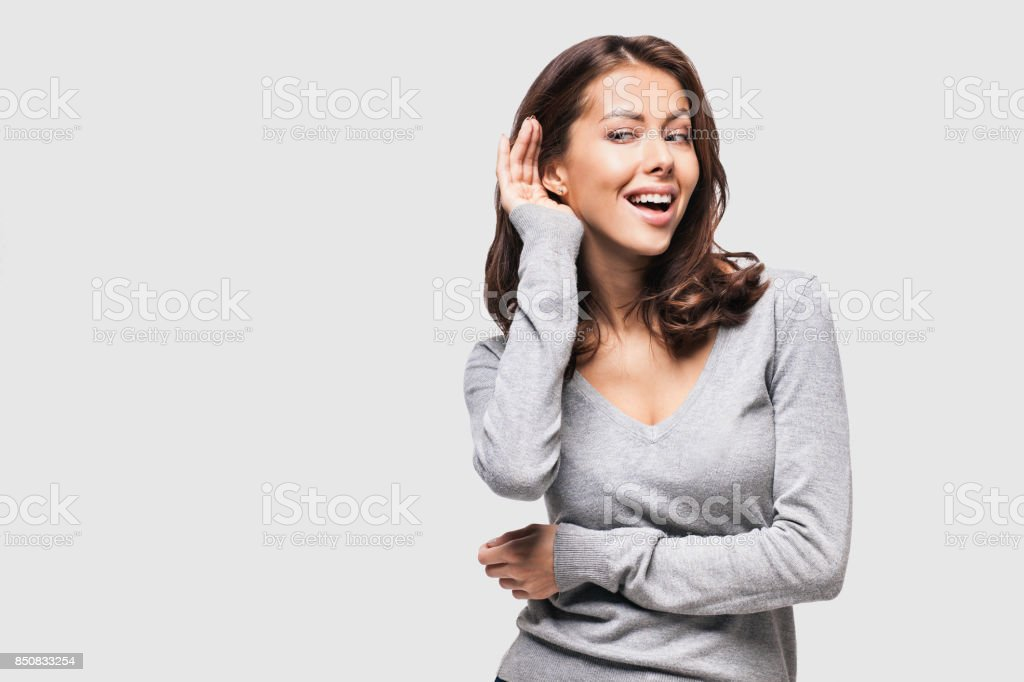 Surprised young woman listening stock photo