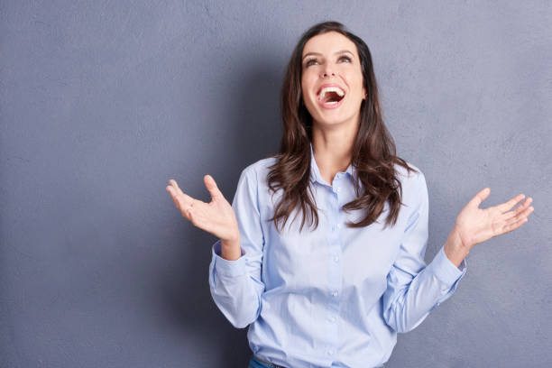 Surprised young woman Shot of a happy relieved and elated woman standing at grey wall. relief emotion stock pictures, royalty-free photos & images