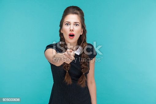 istock Surprised young woman pointing finger at camera and shocked. 925000636