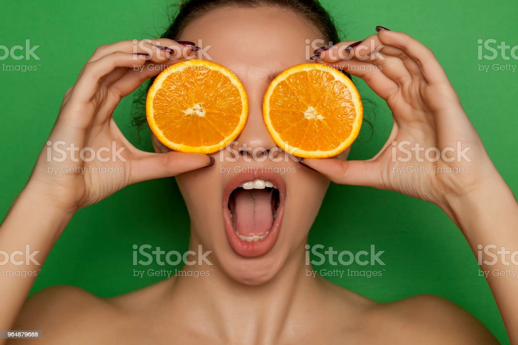 Surprised young woman posing with slices of oranges on her face on green background royalty-free stock photo