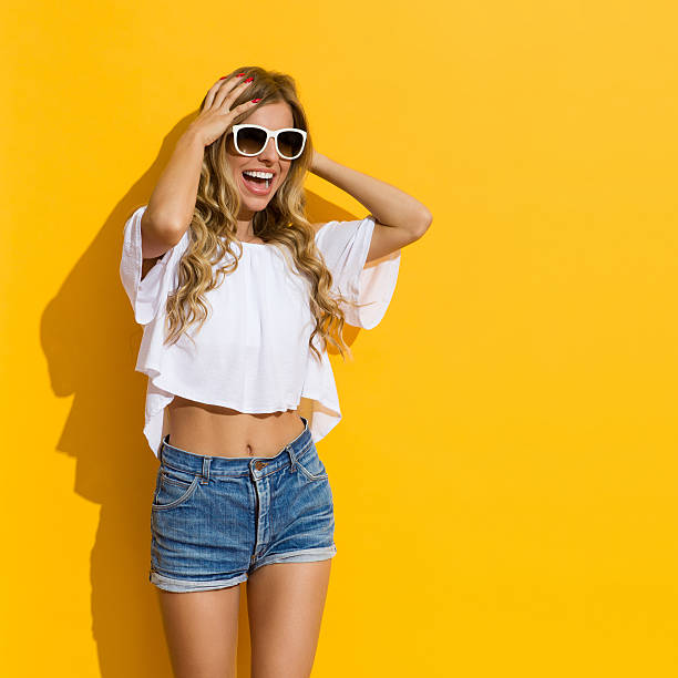Surprised Young Woman Shouting Blond young woman in jeans shorts, white shirt and white sunglasses holding head in hands, shouting and looking away, Three quarter length studio shot on yellow background. shorts stock pictures, royalty-free photos & images