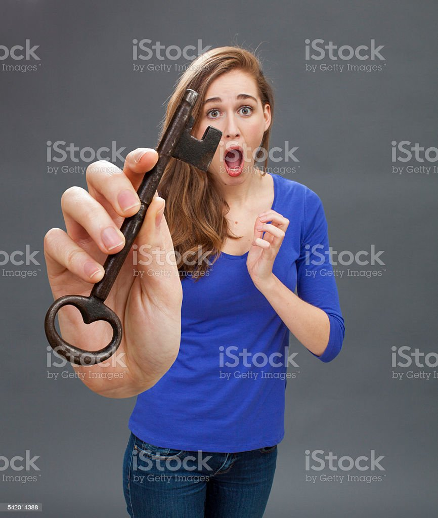 surprised young woman showing a big key for frightening symbol stock photo