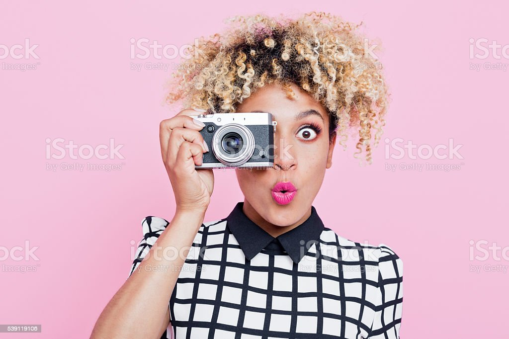 Surprised young woman wearing sunglasses, holding camera Portrait of surprised beautiful afro american young woman wearing grid check playsuit, holding a camera in hand, looking at camera. Studio shot, one person, pink background. Adult Stock Photo
