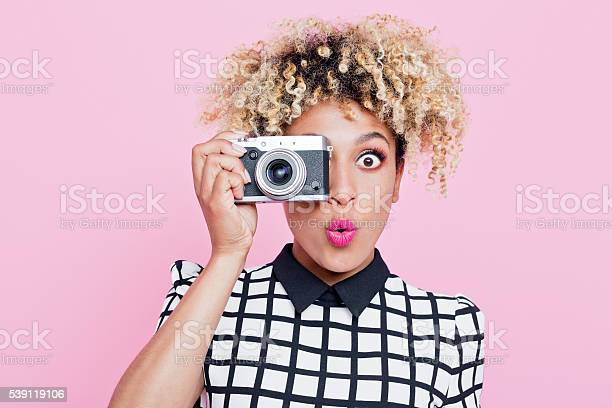Surprised Young Woman Wearing Sunglasses Holding Camera Stock Photo - Download Image Now