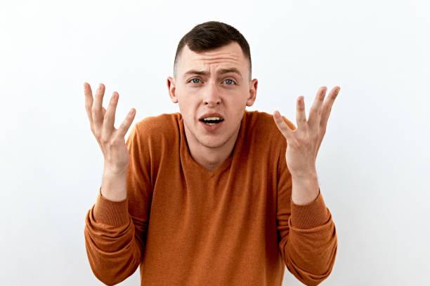 Surpresa, choque, emoção inacreditável. Homem novo na camisola alaranjada, backgraund branco do agaist do retrato da face. - foto de acervo