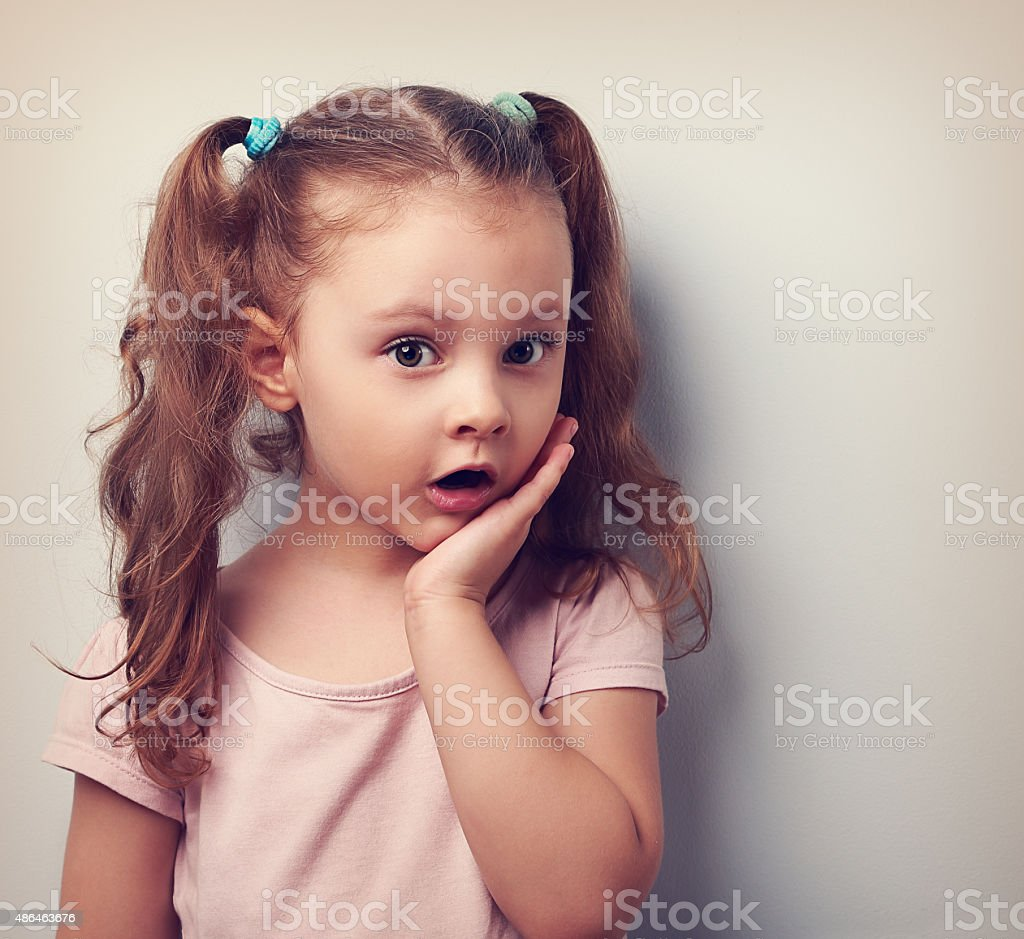 surprising cute kid girl with open mouth looking serious stock photo