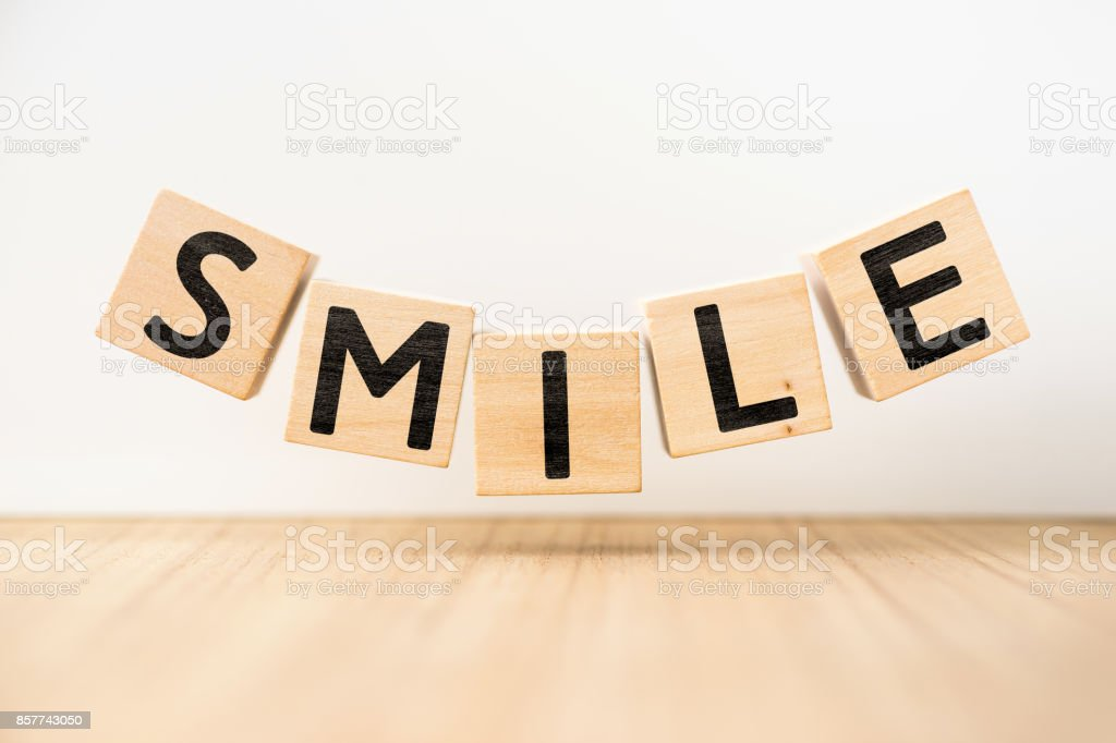 Surreal abstract geometric floating wooden cube with word ' SMILE ' concept stock photo