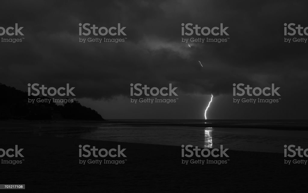 Surreal, amazing lightning penetrating the clouds and hitting the sea stock photo