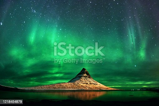 Horizontal shot in Iceland of Aurora Borealis, green and blue colors and stars on the sky, brightly lit in darkness